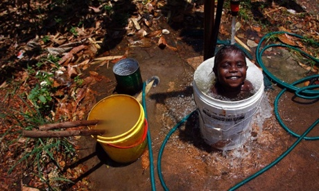 Four-year-old Gregory takes a bath in an old insecticide container at the 'out station' of Ngangalala, located on the outksirts of the community of Ramingining in East Arnhem Land. The Arnhem Land reserve, closer to Bali than Sydney, covers an area of around 97,000 sq kms (37,000 sq miles), has a population of around 16,000 and access for non-Aborigines is by invitation only.