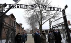 Auschwitz survivors at the infamous gate to the former Nazi concentration and extermination camp