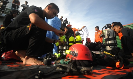 Indonesian navy divers prepare their equipment as the search for the wreckage of the AirAsia jet continues