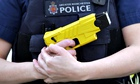 A Greater Manchester police officer holds a Taser stun gun