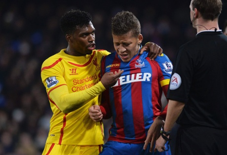 Dwight Gayle is helped up off the ground by Liverpool's Daniel Sturridge.