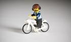 Lego figure with beard and headphones on a bike