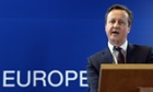 British Prime Minister David Cameron talks to the media at the end of a European Union Summit