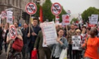 Anti-austerity protesters march down Whitehall during a demonstration on Wednesday after the state opening of parliament.