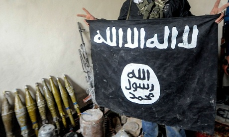A Kurdish fighter in Kobane, Syria, holds up an Isis flag