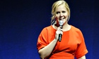 Amy Schumer holding a microphone on a Las Vegas stage