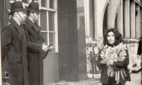 Yoko Ono walking past policemen while carrying daffodils in 1966, after her film 'No. 4 (Bottoms)'  was banned