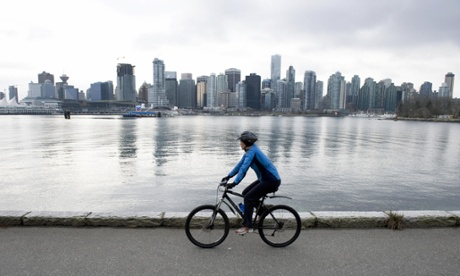 A cyclist observes the skyline of Vancouver.
