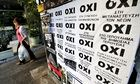 A woman in Athens walks past referendum campaign posters reading
