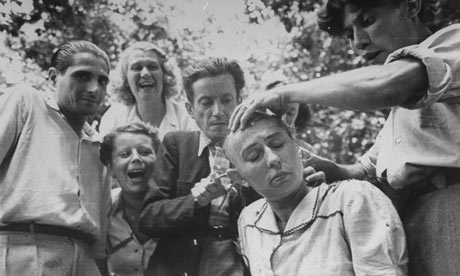 crowd jeers as a woman's head is shaved during the liberation of