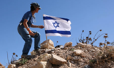 Israeli settler puts flag on a hilltop