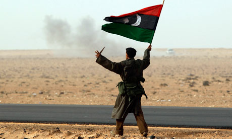 Rebel fighter holds a Kingdom of Libya flag