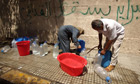 Tripoli residents fill plastic jerry cans with water