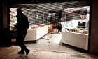 A policeman walks past a damaged jewellery shop in Enfield