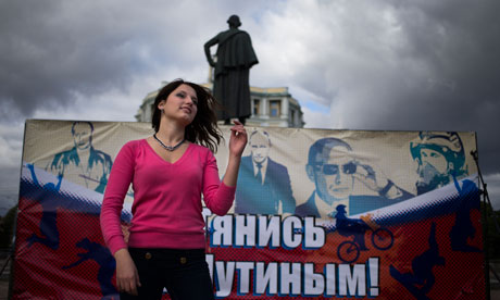 A pro-Kremlin activist in Moscow dances in front of a poster depicting the Russian president on his 60th birthday.  Photograph: Alexander Zemlianichenko/AP