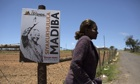 A woman walks by a poster with an image of former South African president Nelson Mandela in Qunu