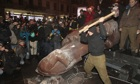 A protester swings a hammer at the fallen statue of Lenin in central Kiev