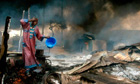 Man rinses soot from his face at the scene of a gas pipeline explosion in Nigeria