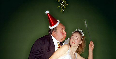 A boss trying to kiss an employee under the mistletoe at the office christmas party