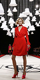 A model wears a red wrap dress on the catwalk during the Paul Smith fashion show at London Fashion Week