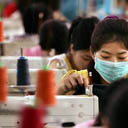 Chinese workers sew t-shirt in a textile factory in south China