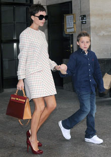 Victoria Beckham with a Hermes bag and child