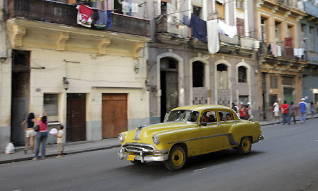 A vintage yellow car drives past buildings in old Havana, Cuba