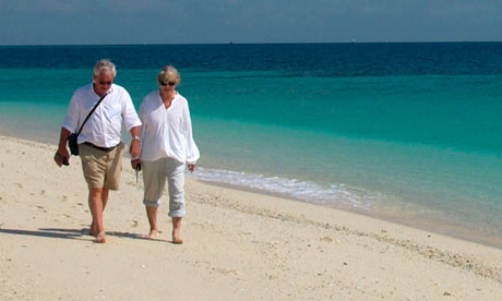 An elderly couple walk along a beach Singles holidays are a great way to