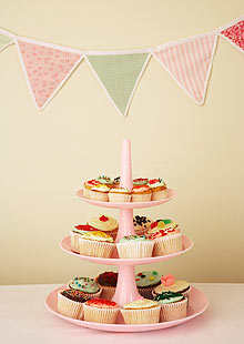 Cup cakes on cake stand under bunting