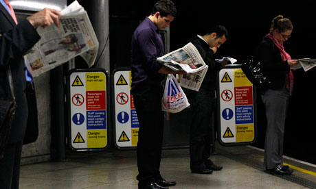 Commuters read London evening papers