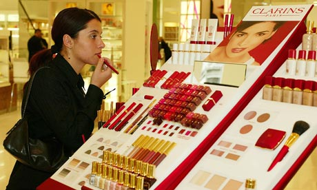 A woman tries on lipstick at the Clarins stand