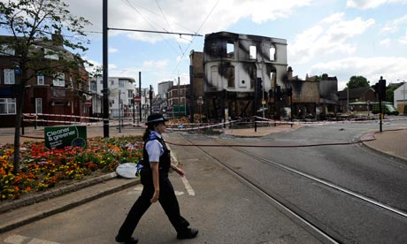 London riots: a police officer passes the remains of a burnt out furniture shop in Croydon. Photograph: Facundo Arrizabalaga/EPA