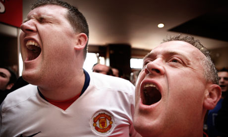 Manchester United fans watch football in a pub