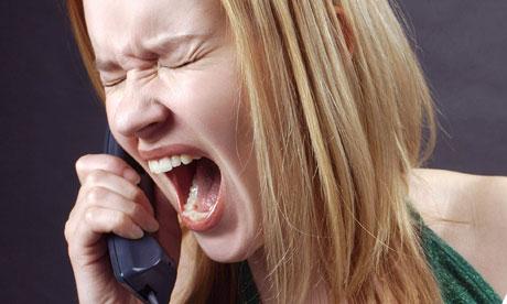 A woman shouts into a phone