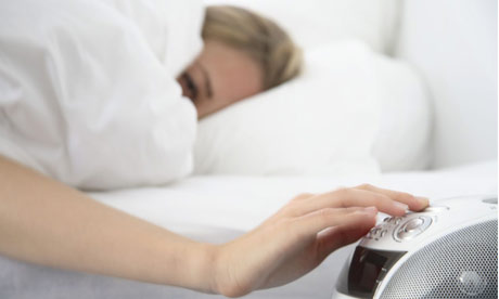 Woman in bed turns off alarm clock