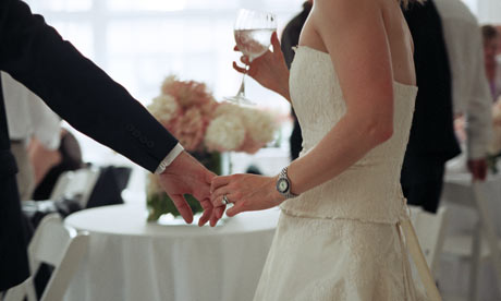 Newlyweds holding hands at a wedding reception