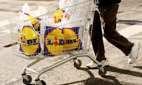 A shopper pushes a trolley with Lidl carrier bags