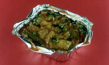A takeaway vegetable curry in a tin foil tray