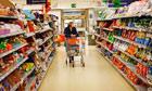 A shopper walking down a supermarket aisle