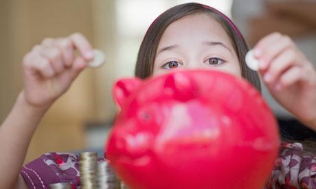 A girl putting money in a piggy bank