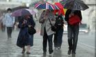 People with umbrellas walk through rain in London.