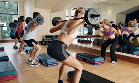People working out with weights at a gym studio