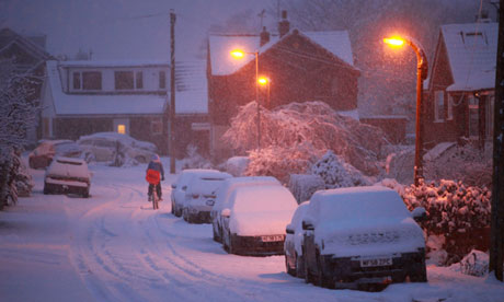 A newspaper delivery boy cycles in the snow in Greater Manchester