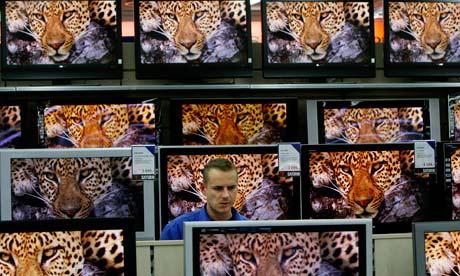A salesman standing among flatscreen TVs