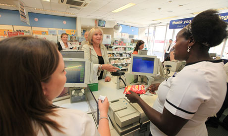 Guardian Money reporter Jill Papworth tries out contactless payment in a Boots store in London, UK