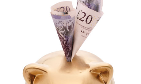 A golden piggy bank with £20 notes