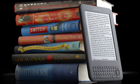 A Kindle and a pile of books