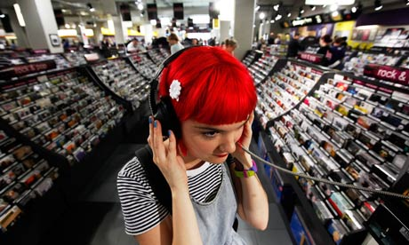 A womnan listening to music on headphones in HMV, London