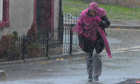 A woman walking through heavy rain
