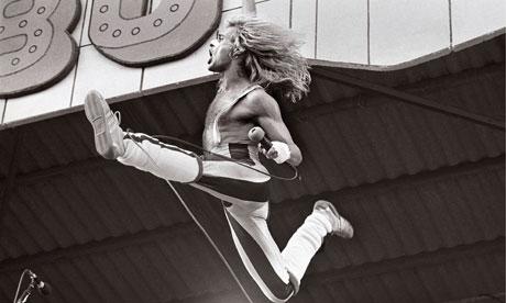 David Lee Roth, of Van Halen, performing live onstage, jumping.